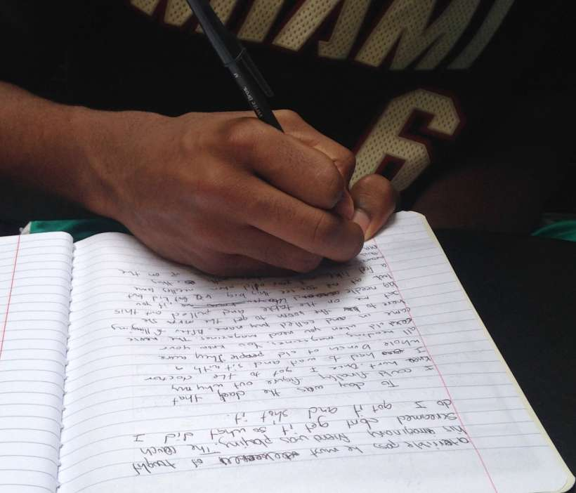 Hand free-writing essay in notebook